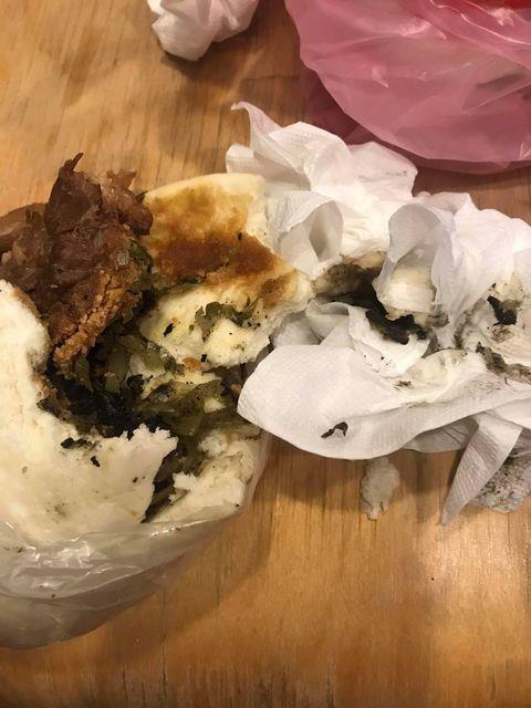 有網友分享,自己因居家檢疫無法出門,便用外送平台點了刈包套餐,但當餐點送到時卻發現刈包裡除了酸菜及配菜,還夾雜很多黑色的屑屑,才發現裡面竟然有菸灰。 圖/爆料公社