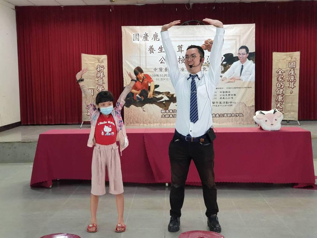 臺中慈濟醫院中醫部陳智聖醫師(右)現場教導民眾雙手攀足固腎腰的運動。