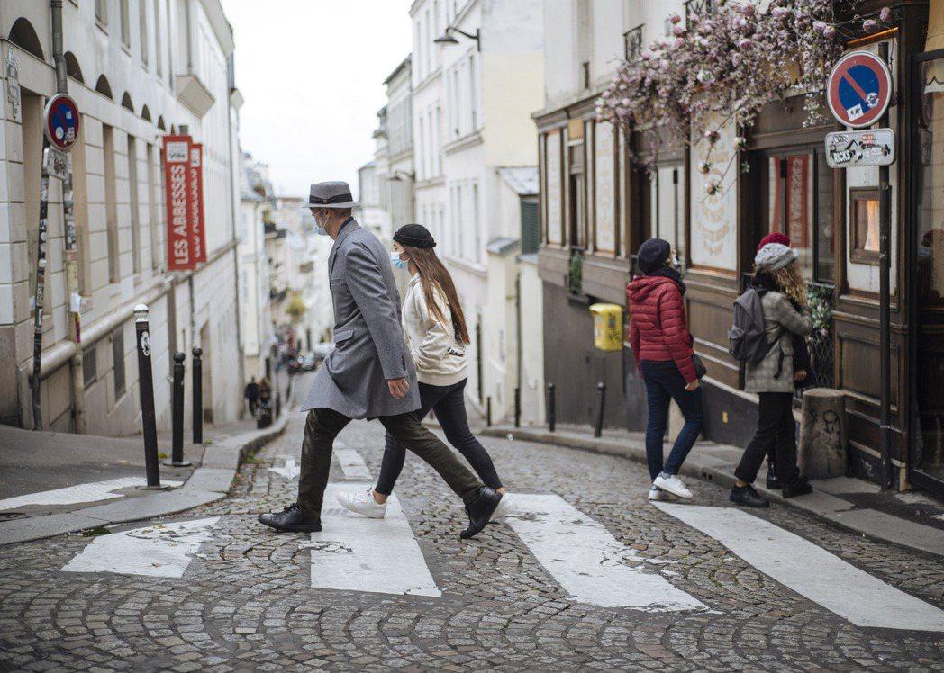 路人25日戴口罩經過巴黎蒙馬特地區。(美聯社)