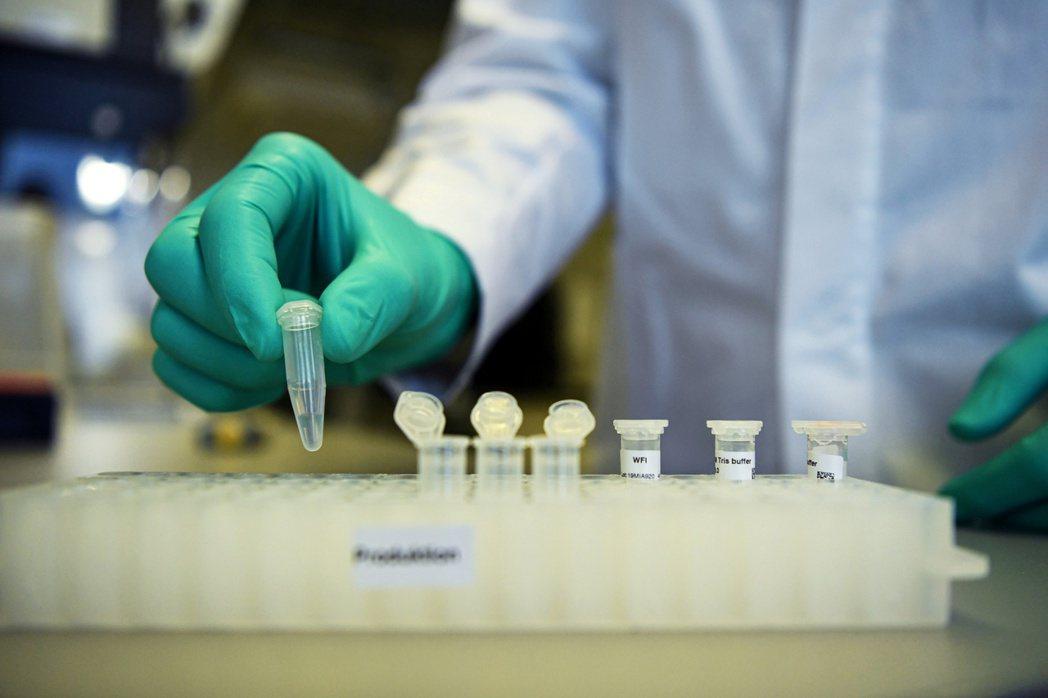 德國一家製藥公司職員在圖賓根市實驗室,解說研發新冠疫苗的流程。(路透)