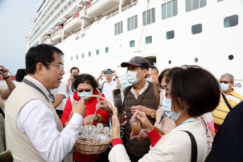 台南市長黃偉哲(左)昨天迎接搭乘「探索夢號」郵輪的遊客,並送上小禮物。圖/市府提供