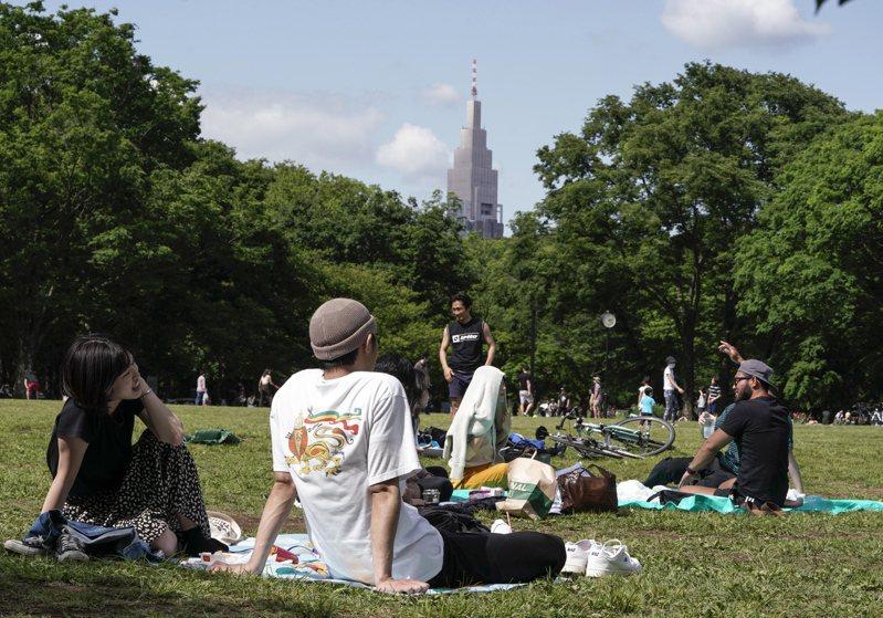 今年跨年,日本勞工可能享有創紀錄的17天連續假期。圖為在東京代代木公園休憩的民眾。(歐新社)