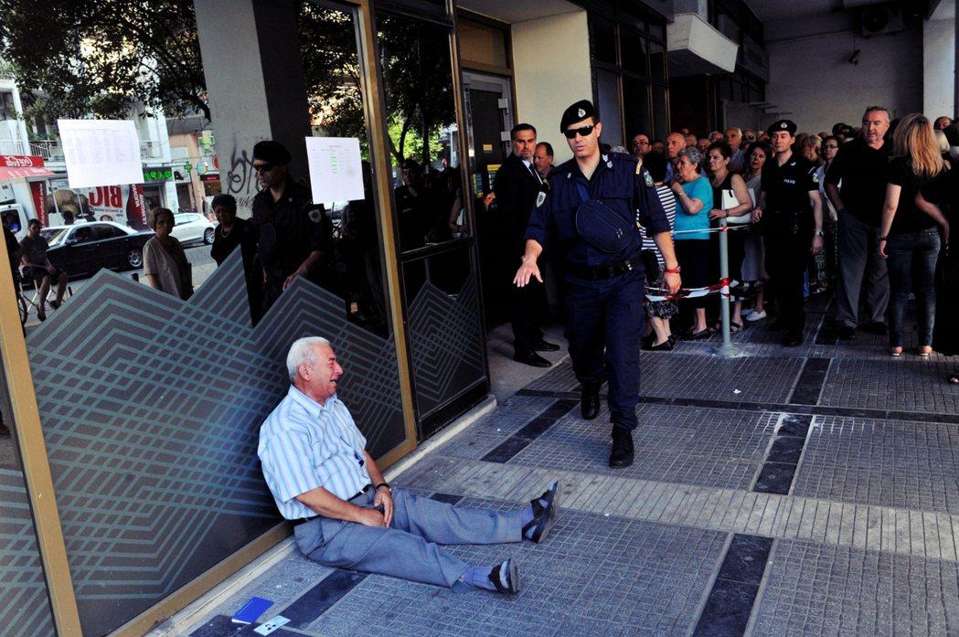 希臘經濟持續衰退,引起社會普遍不滿。圖為2015年一名男人坐在希臘的一家銀行旁,...