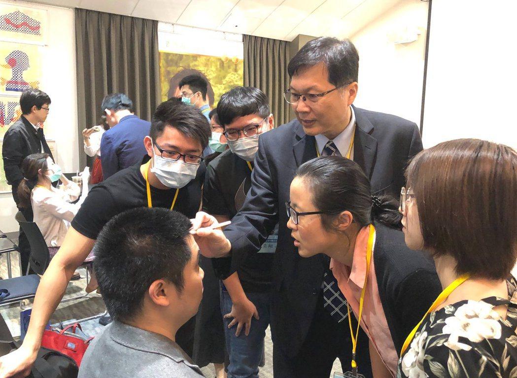王正坤醫師先拿筆在臉上,畫出注射肉毒桿菌素的危險區域,並與其他醫師做經驗交流。...