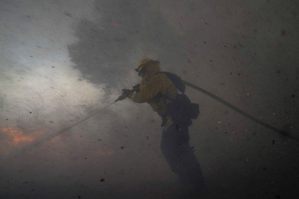 強風助長下,美國南加州野火肆虐,26日重傷橘郡2名消防員。美聯社