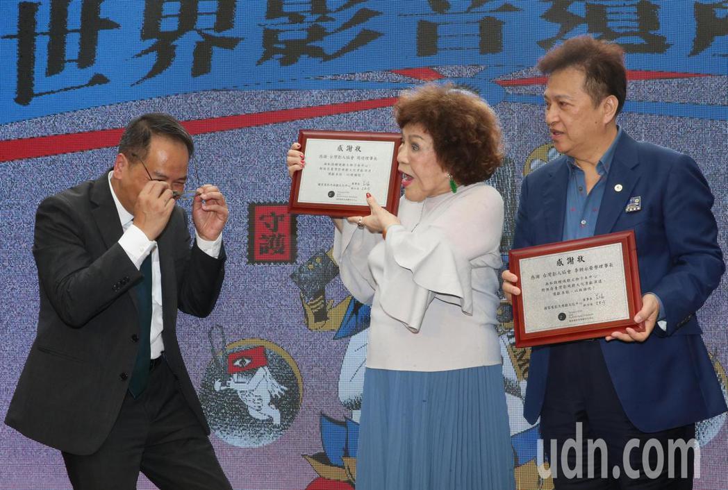 捐贈多項影視作品的台灣影人協會理事長周遊(中)與夫婿李朝永(右)獲頒感謝狀時,周