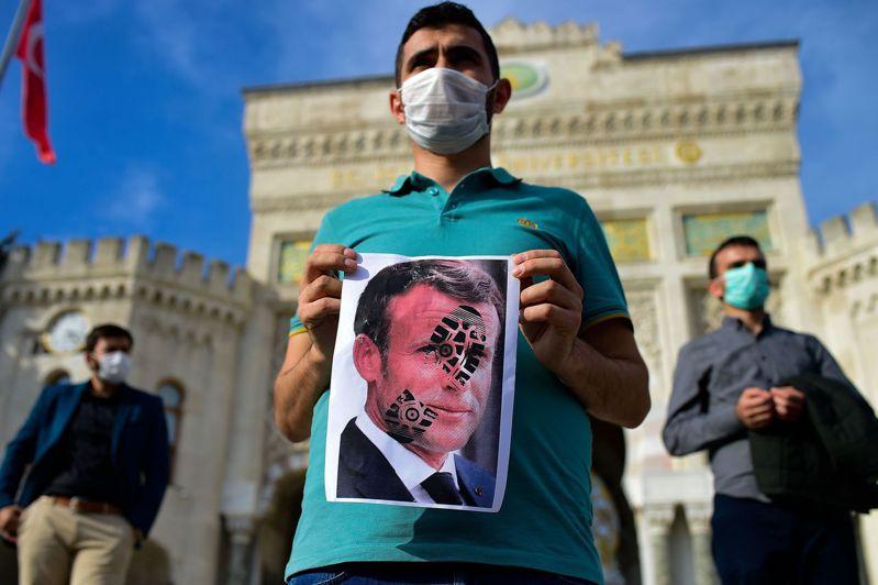 土耳其民眾25日在伊斯坦堡,舉著一個鞋印踩在法國總統馬克宏臉上的海報,抗議馬克宏支持言論自由,允許跟伊斯蘭教先知有關的諷刺漫畫。法新社