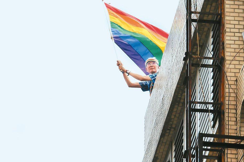 許多人對於祁家威的印象就是喜歡在同志遊行時,爬到高處,揮舞彩虹旗。圖為2018年...