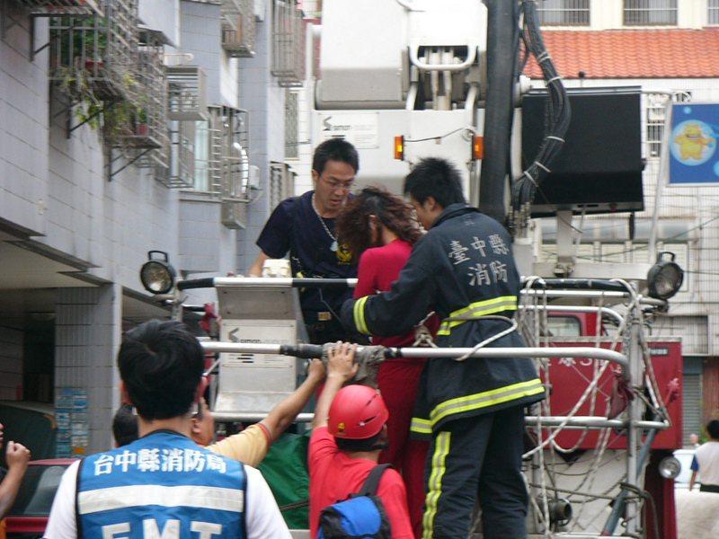2007年台中一名高姓女子穿紅衣想跳樓輕生,消防隊員冒險搶救。圖/聯合報系資料照片