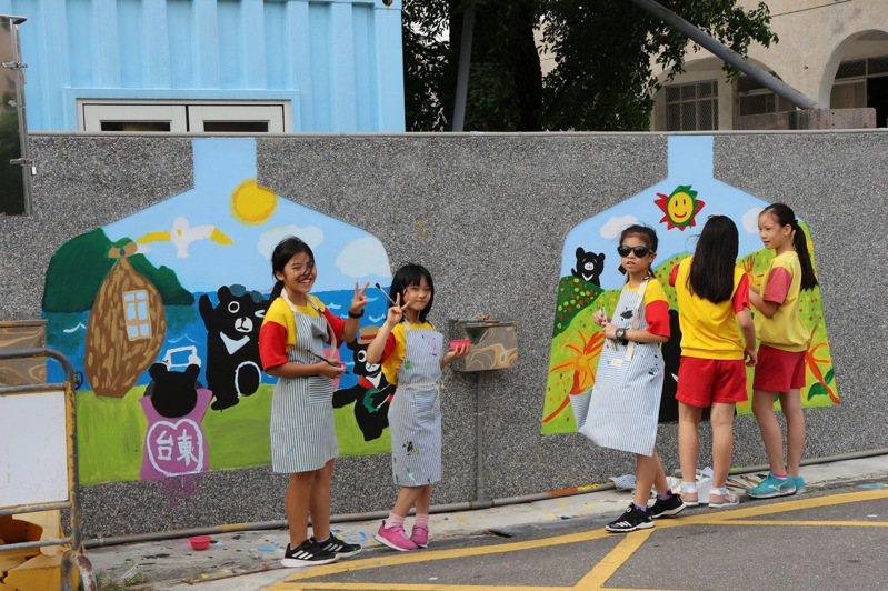 國立台東大學附設實驗小學美術班學童,昨天與彩繪專家協力合作,完成校園圍牆彩繪。圖/台東縣政府提供