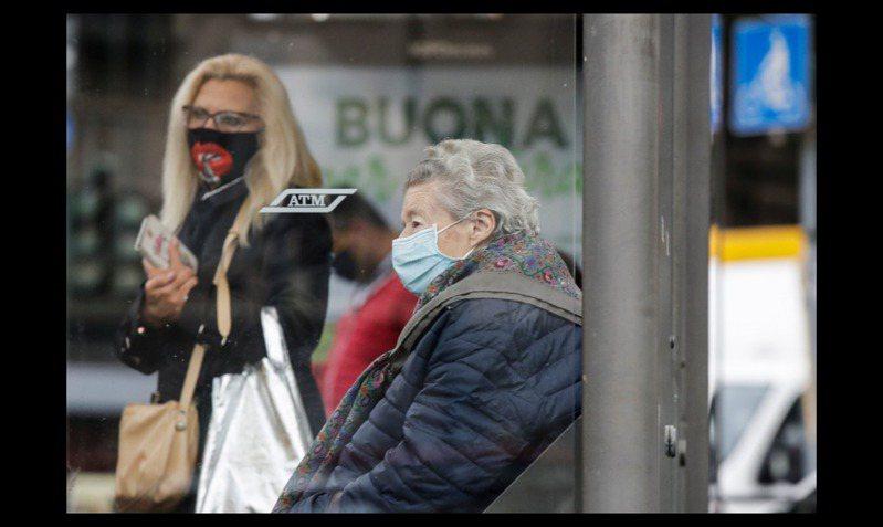 義大利爆發新冠肺炎第二波疫情,圖為米蘭街頭民眾戴上口罩防範病毒傳染。美聯社