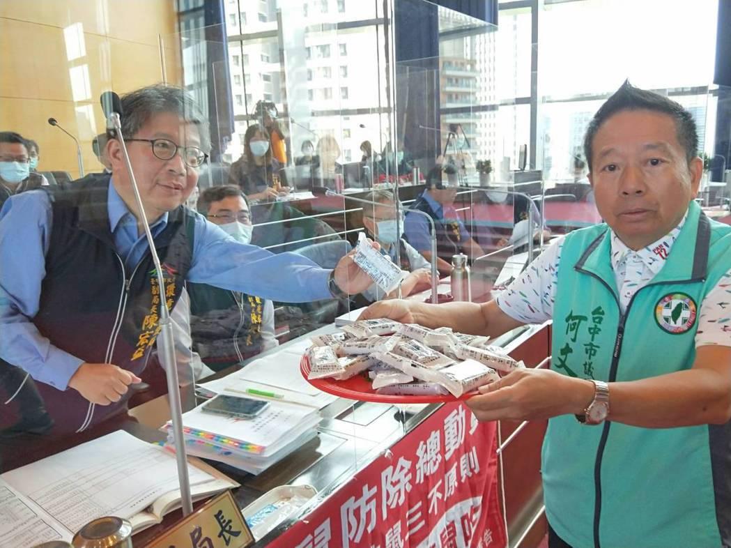 台中市議員何文海(右)將里長退貨的老鼠藥,拿給環保局代局長陳宏益看。記者張明慧/...