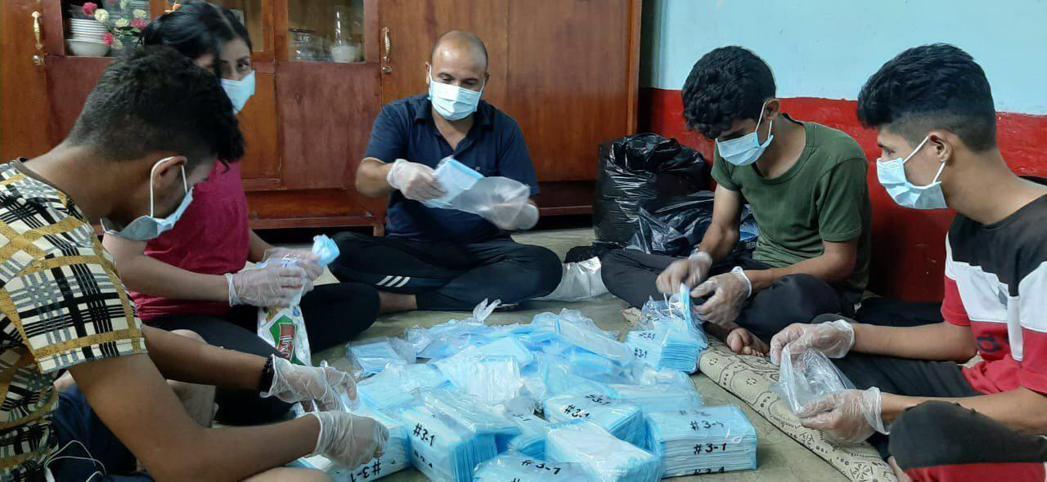 伊拉克當地工作人員協助分裝與配發我國捐贈口罩。圖/外交部提供