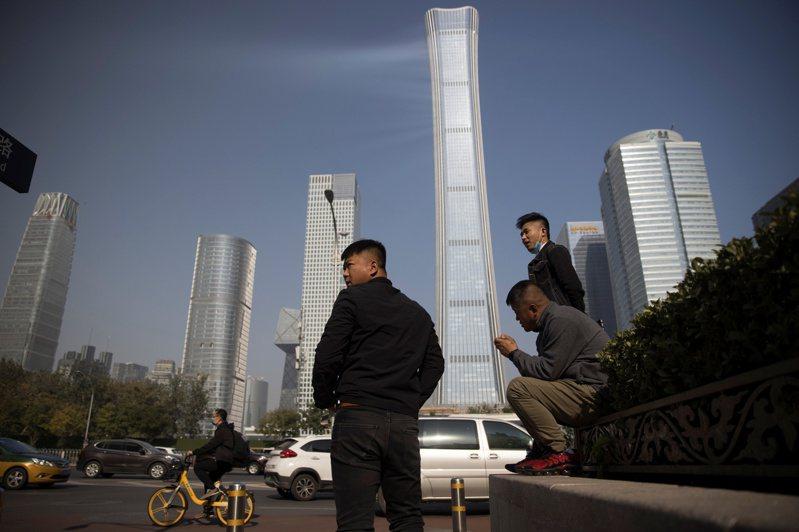 中共十九屆五中全會審議通過十四五規劃和二○三五年遠景目標的建議,擘畫大陸未來經濟社會發展路線圖。圖為北京商務區在路旁等待的民眾。(路透)
