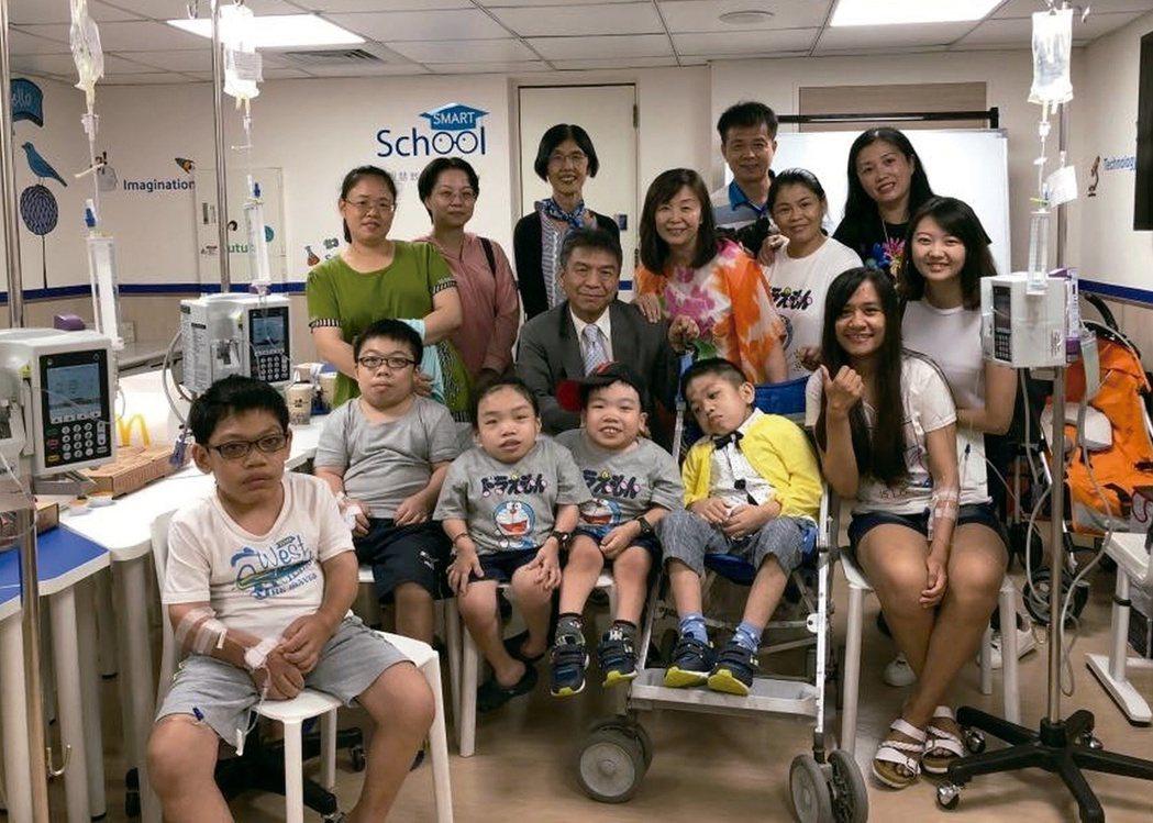 第30屆醫療奉獻獎得主、中國醫藥大學副校長蔡輔仁(中)與罕見疾病患者、家屬像多年...