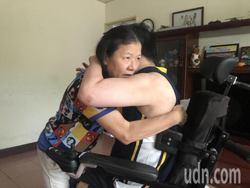 陳心惠(左)身材瘦小,每天得將身高180公斤、體重近百公斤的兒子從床上抱到輪椅,靠的是護腰束帶和瞬間施力。記者曾健祐/攝影