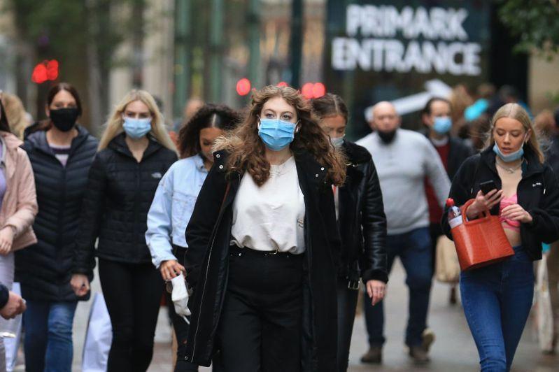 英格蘭地區北部西約克郡里茲的民眾卅日戴著口罩逛街購物。(法新社)