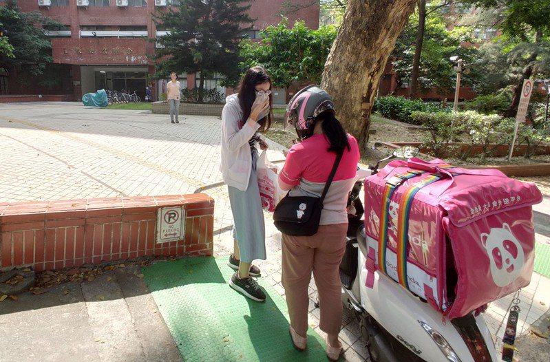 外送員到中山大學宿舍外送餐,必定等顧客現身才拿出餐點。記者蔡容喬/攝影