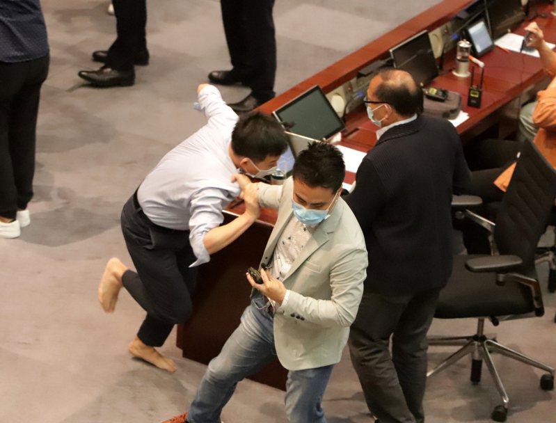 香港立法會內委會5月8日改由建制派議員主持會議,泛民議員不滿並阻撓會議進行。圖為泛民議員陳志全被建制議員單手強行拖走。中央社資料照片