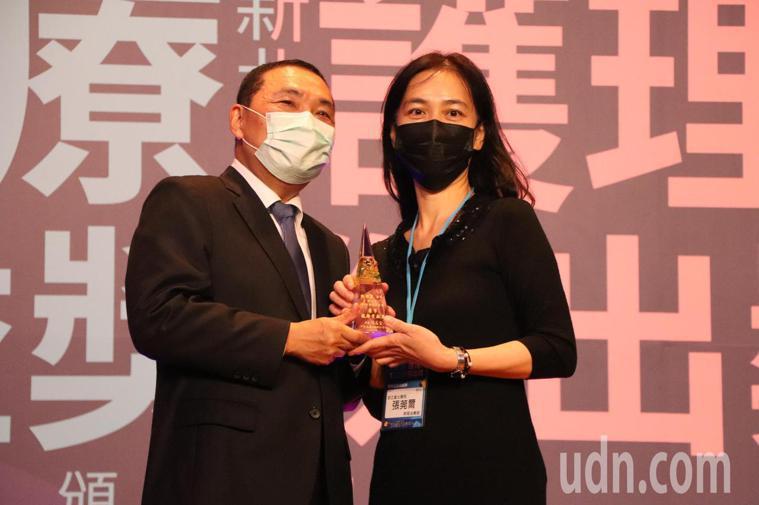 新北市長侯友宜頒發「醫事服務貢獻獎」給護理師張莞爾。記者吳亮賢/攝影