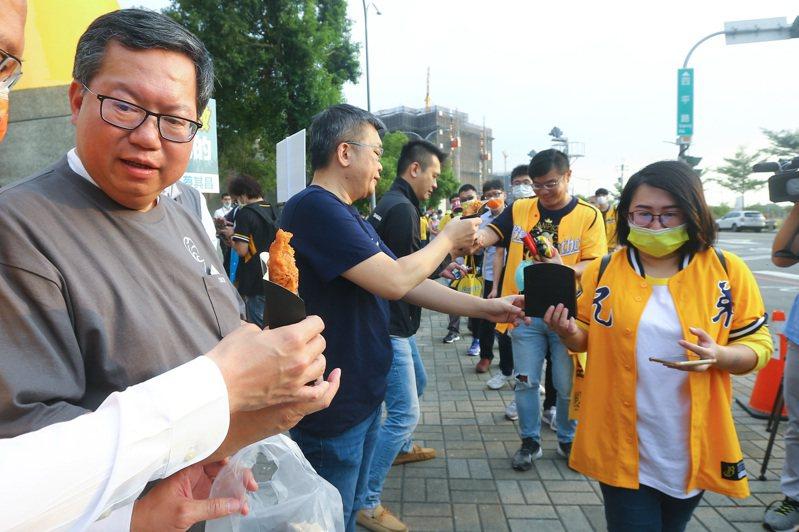 桃園市長鄭文燦(左一)陪同立法院副院長蔡其昌(左二)發放雞排給球迷。記者黃仲裕/攝影