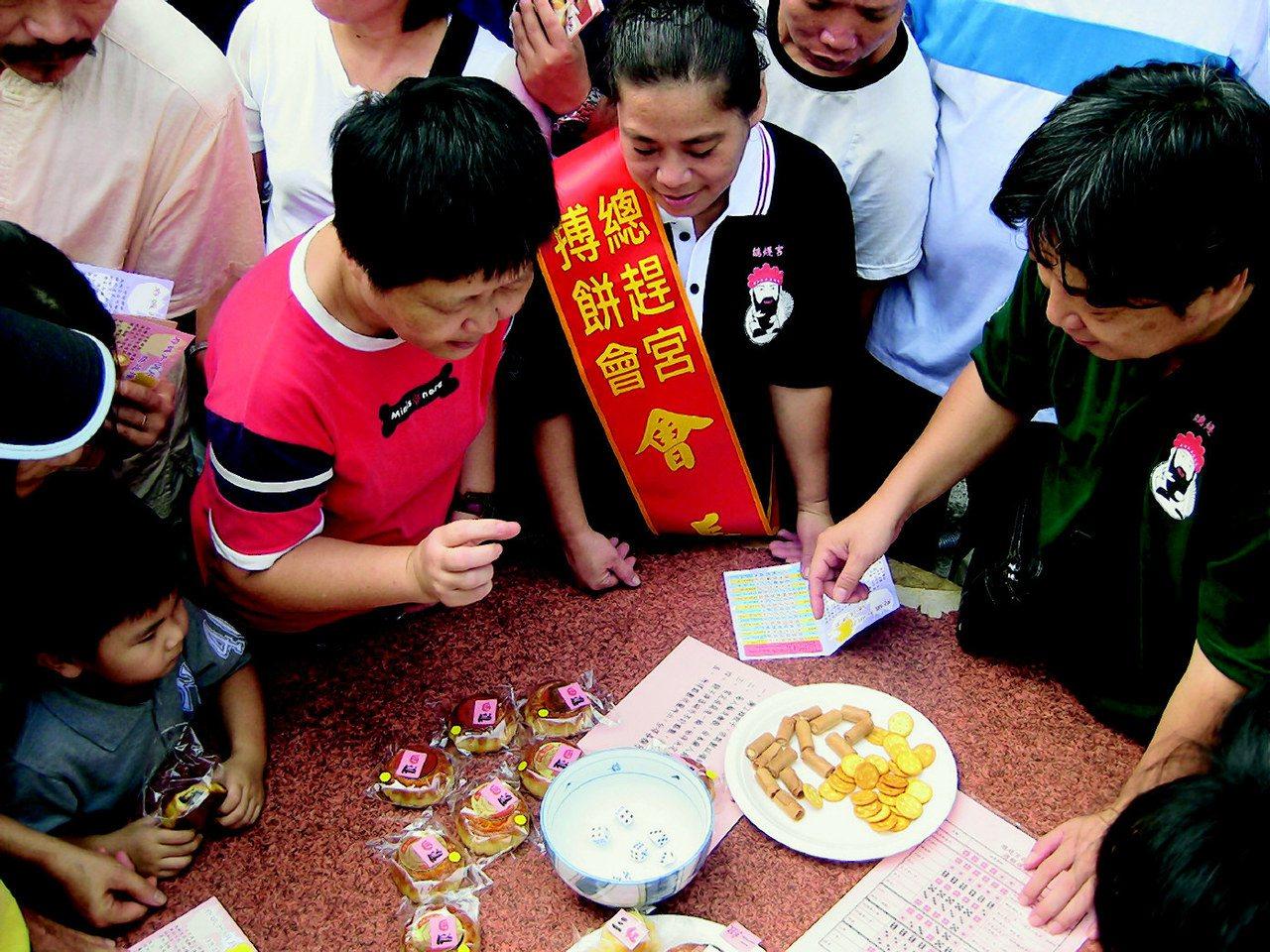 南市三級古蹟總趕宮舉辦中秋搏餅活動,吸引男女老幼擲骰子搏月餅。 圖/黃宣翰 攝影