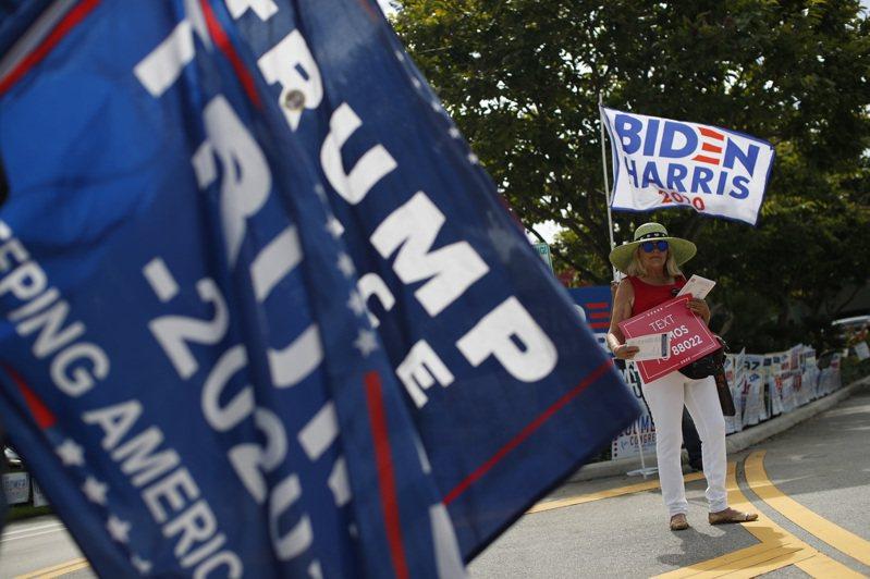 美國選民揮舞著川普及拜登的競選旗幟。 美聯社