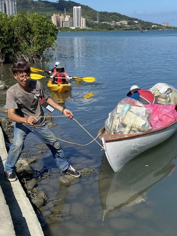 陳明忠(左)拉回滿載廢棄物的木船。 圖/許祖菱 攝影