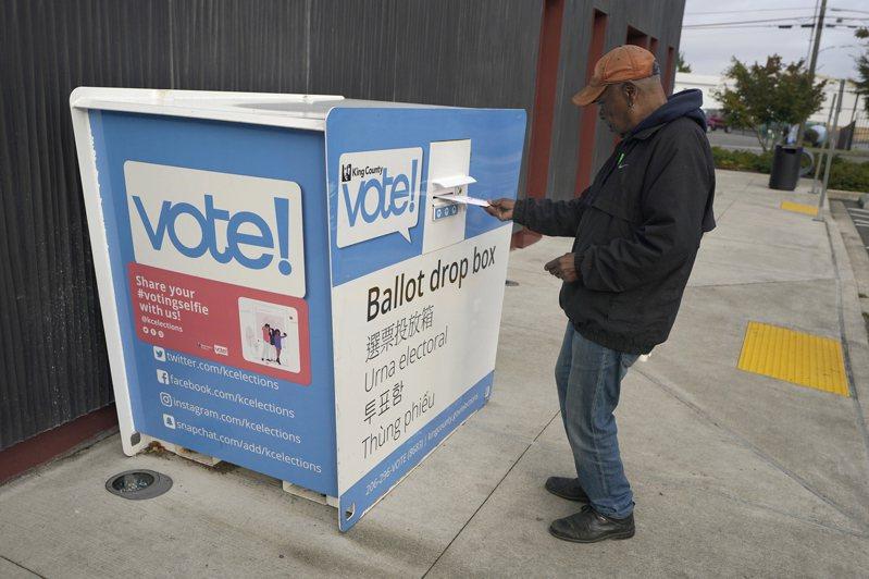 美國許多地方設選票投遞箱,方便選民郵寄投票。西雅圖一名選民將選票投入投遞箱。美聯社