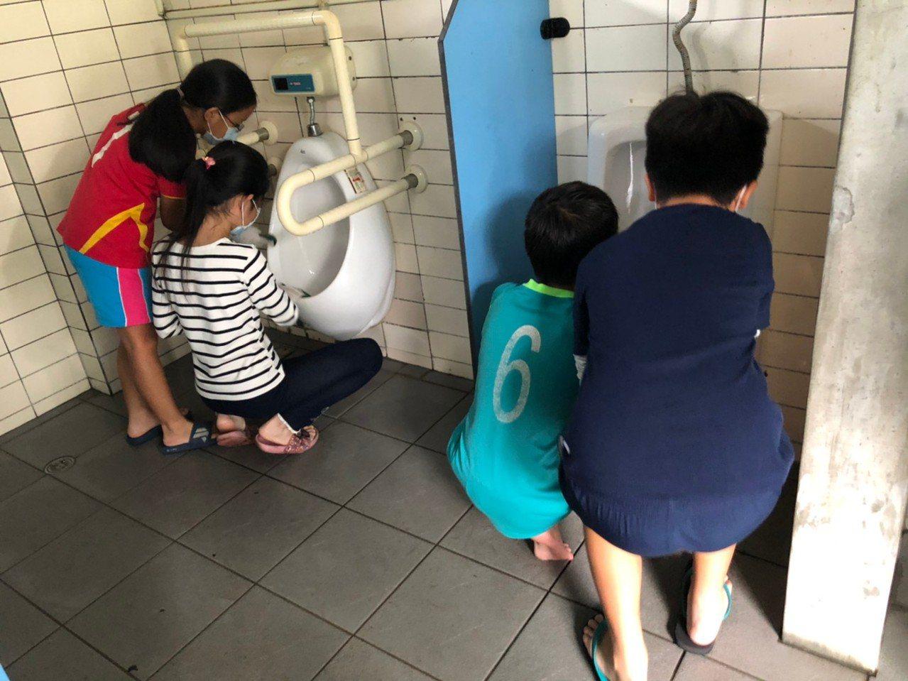 大小志工用手探入便斗深處,挖出陳年髒污,徹底清掃。 圖/台灣美化協會提供
