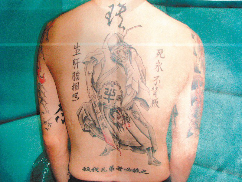 頭號槍擊要犯「牛皮」王俊偉背上整面刺青,透露為老大吳東皇報仇決心。記者蔡佳妤/翻攝