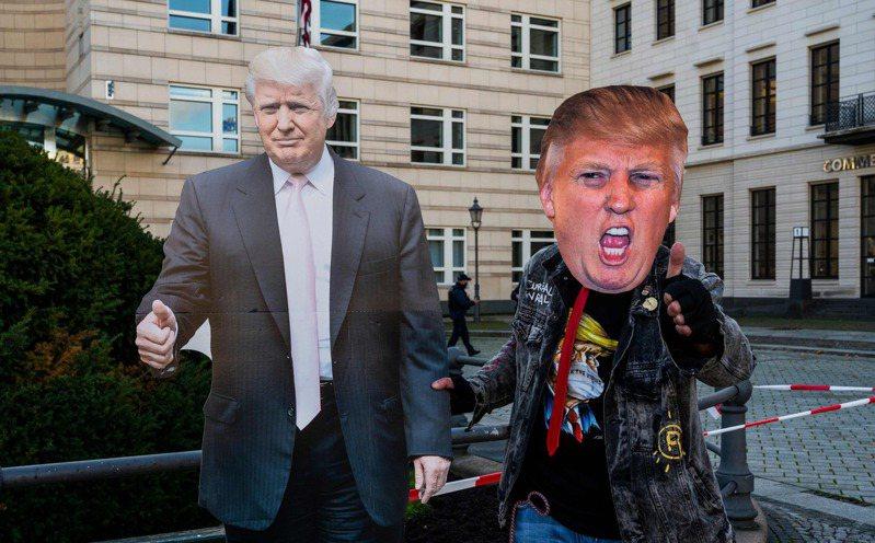 川普的支持者(右)4日在德國柏林美國大使館前戴上川普面具,與川普的人形立牌(左)合影。(法新社)