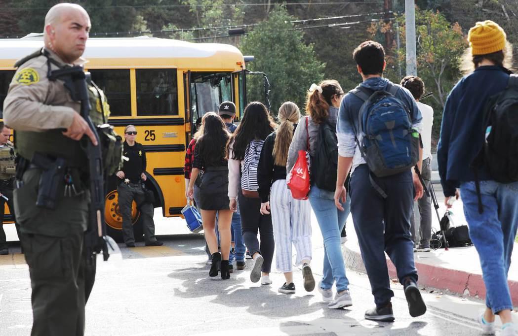 科倫拜事件的20年後,2019年索格斯高中發生槍擊案,警方荷槍護送學生離校(圖為...