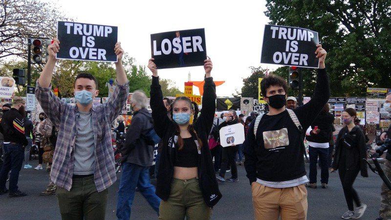 民主黨候選人拜登勝出機率升高,支持者在白宮前高舉標語表示美國總統川普已經出局。中央社
