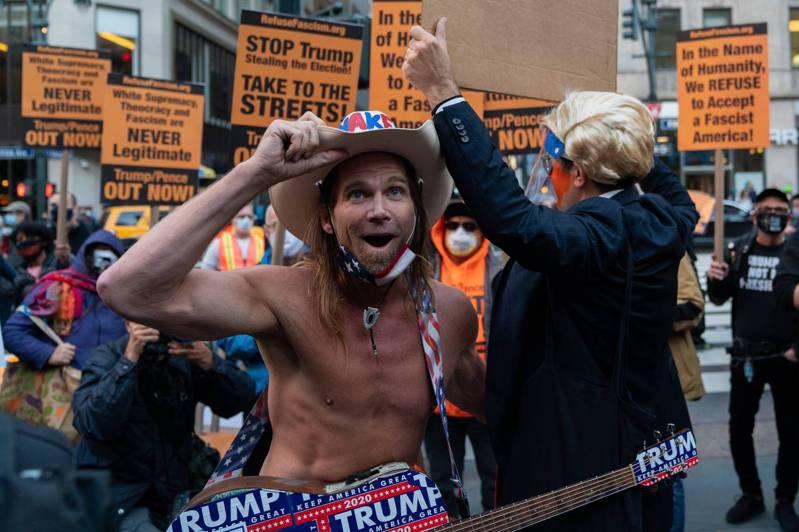 紐約市民眾4日發起示威,標語牌上寫著「阻止川普偷選票」。現場一名川普總統的支持者,光著上身彈吉他。法新社