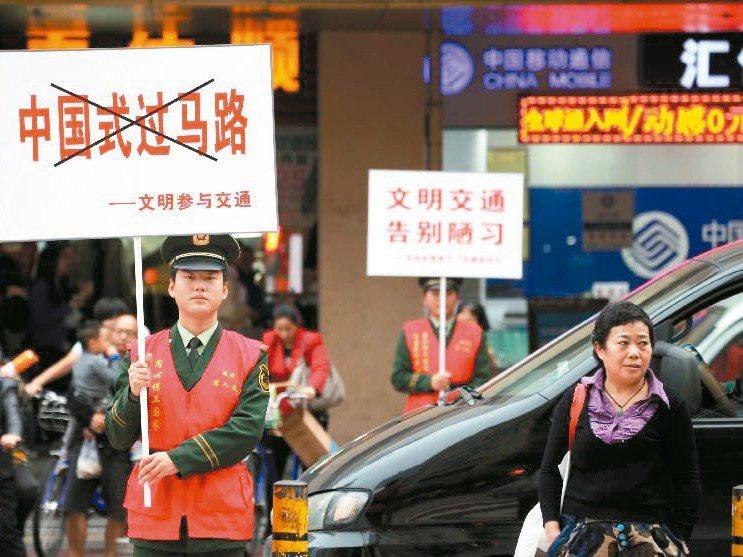大陸對交通違規的處罰愈來愈重。圖為官方宣導「遵守交通信號、安全文明出行」。圖/摘自新華網