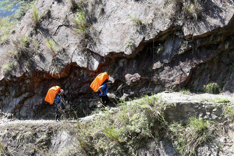 在登山口打包完畢,俗稱「揹工」的高山協作員出發上山,保麗龍箱內裝滿了要背上山的食材。記者邱德祥/攝影