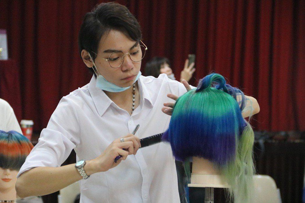 弘光美髮系學生蘇冠霖領取助學金專心比賽。 弘光科大/提供。