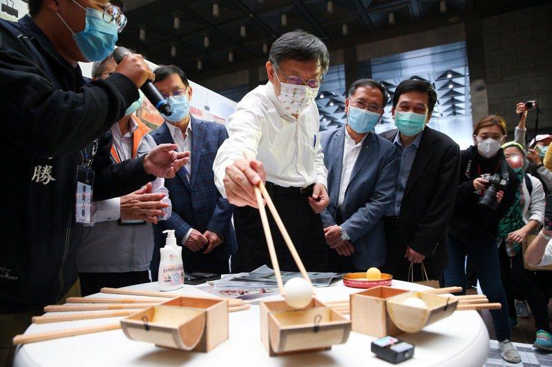 台北市長柯文哲(中)出席「2020台北社造季」聯展,試著用長筷子夾起乒乓球。記者余承翰/攝影