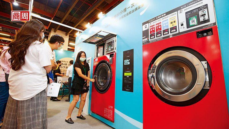 10月台北國際加盟展中,自助洗衣店加盟總部員工,正向加盟主說明洗脫烘三合一的洗衣設備優勢。(攝影者.駱裕隆)