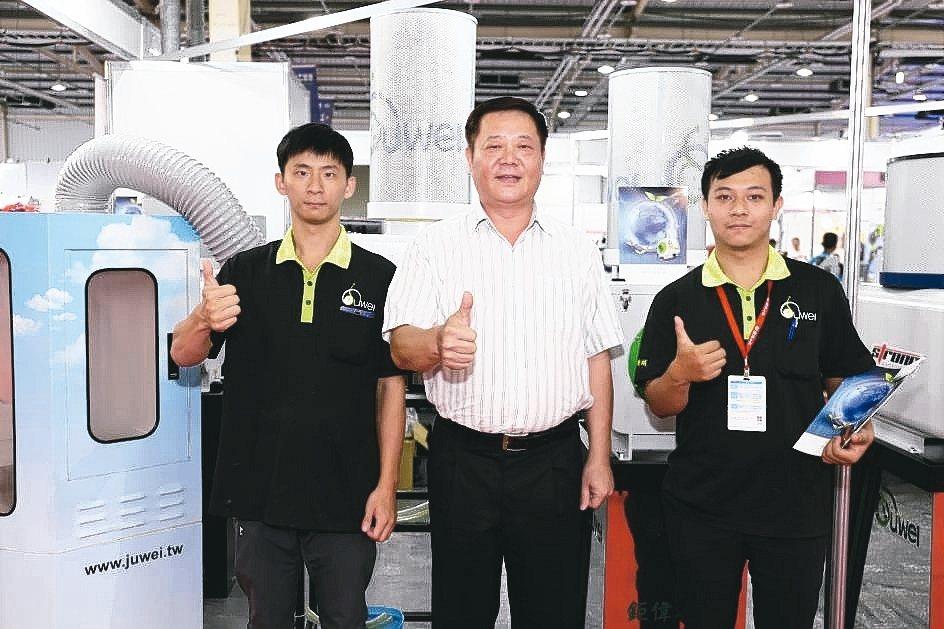 鉅偉機械董事長徐志溢(中)與夥伴在展場合影。 黃奇鐘/攝影