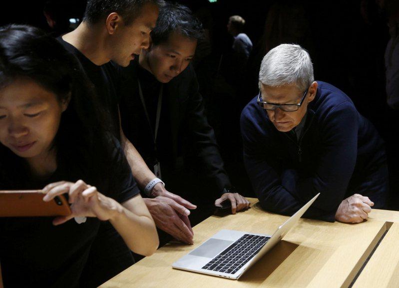 新款MacBook Pro發表會上,蘋果執行長庫克(右)看著同仁示範操作。 路透