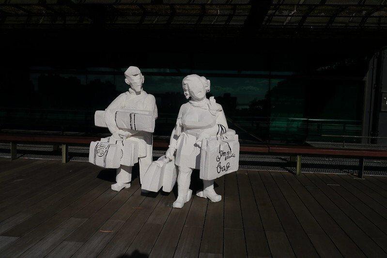 雕塑大師朱銘「白彩人間」的雕塑品,提著採購戰利品的男女。