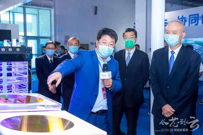 紫光集團董事長趙偉國(前)今年9月在北京科博會紫光展位上,向北京市委書記蔡奇(右一)介紹紫光在存儲晶片、5G晶片等領域的最新發展成果。(取自紫光集團官網)
