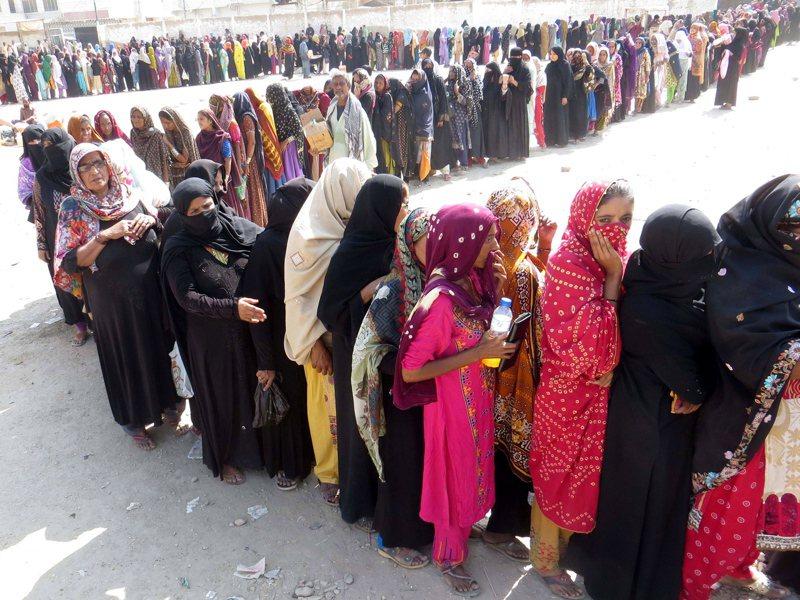 巴基斯坦經濟受新冠疫情重創,大城海德拉巴市的婦女大排長龍領取急難救助金。(歐新社)