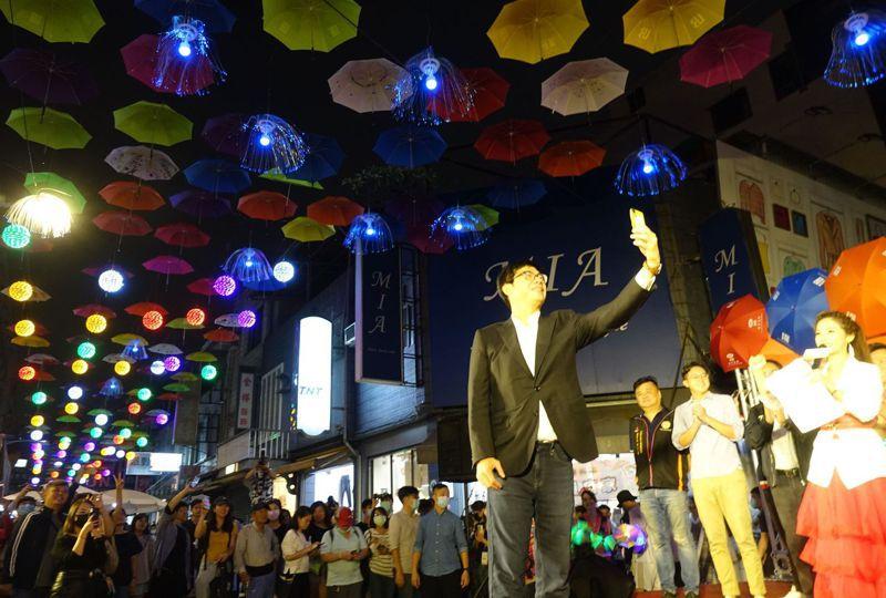 高雄市後驛商圈用傘、燈營造特色,昨晚一點燈,滿街絢麗,高雄市長陳其邁(前)立刻拿起手機自拍。記者楊濡嘉/攝影