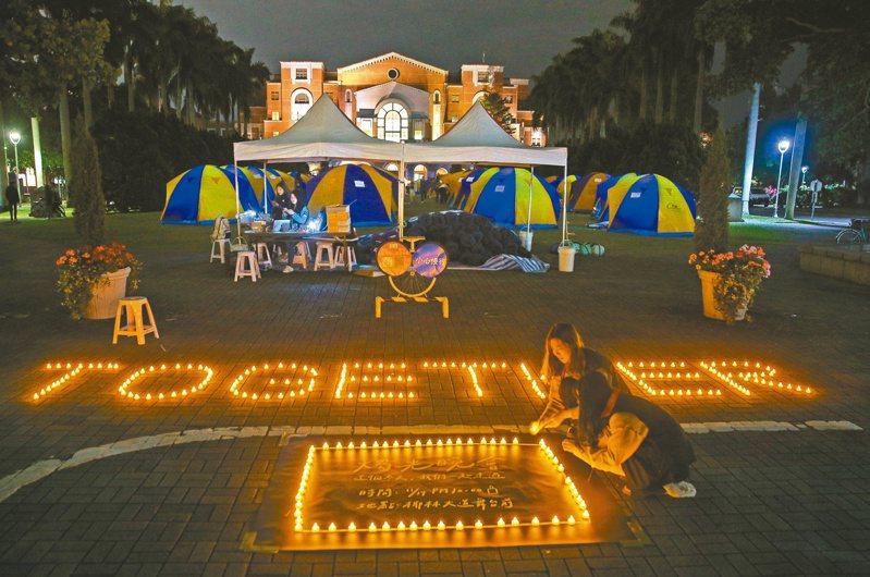 台灣大學近日接連發生學生輕生事件,氣氛低迷,台大學生會昨晚在校園內舉行燭光晚會,在地上點亮排著「TOGETHER」的燭光,並寫著「這個冬天,我們一起走過」。記者余承翰/攝影