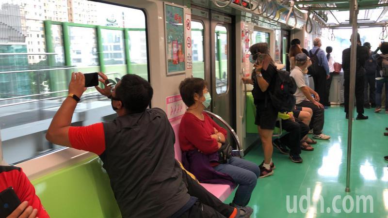 台中捷運昨起試營運,不少人拿手機拍照留念。記者陳秋雲/攝影