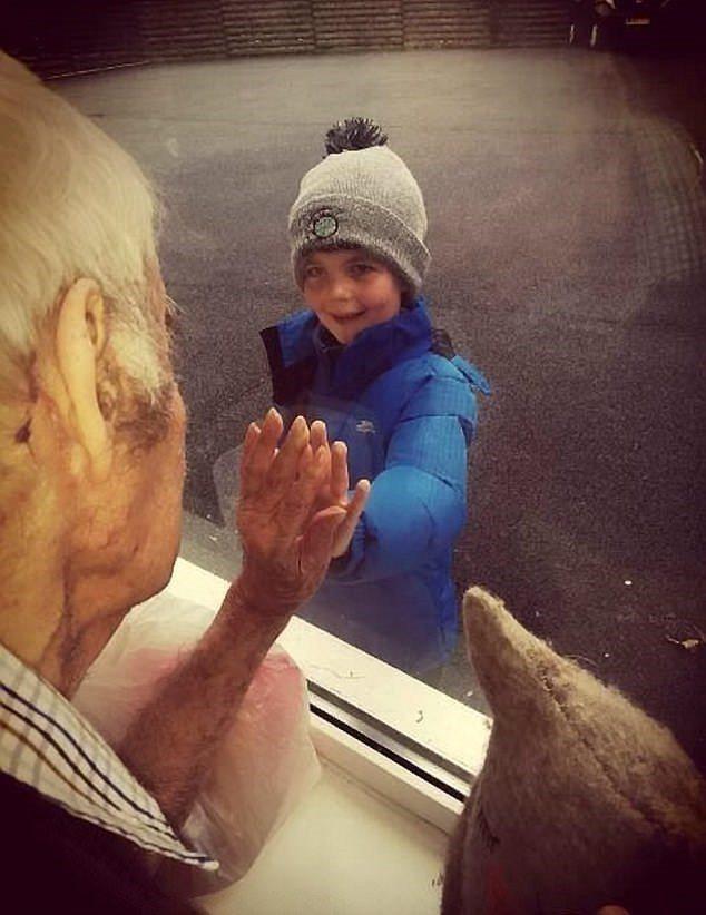 英國7歲男童跟素昧平生的93歲阿公藉通信發展出友誼。上周兩人終於隔著養老院的窗戶首次見面。圖/取自dailymail