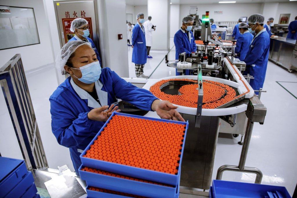 圖為工作人員在中國Sinovic機構裡製作和包裝疫苗。 圖/歐新社